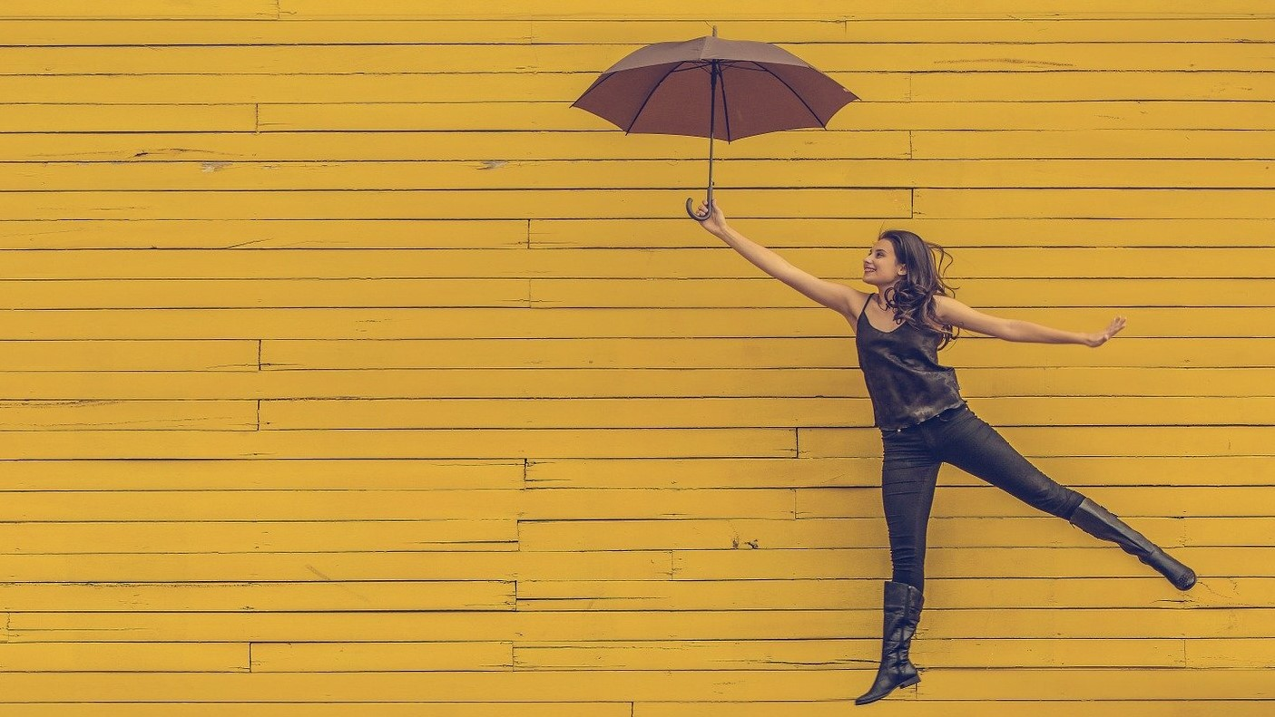 Image: Person jumping next to a yellow wall, holding an umbrella