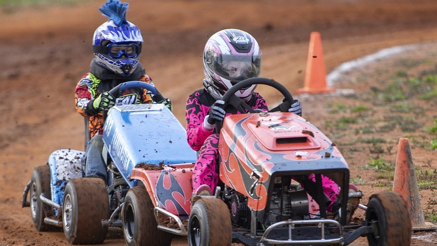 Image: Two people competing in a lawn mower race