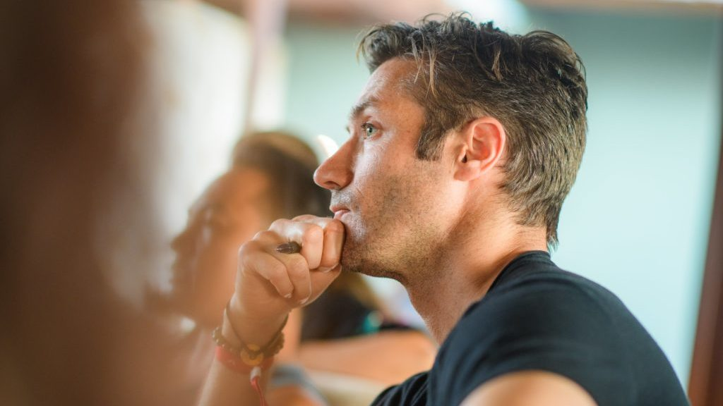 Image: Man in class with hand on chin, thinking.