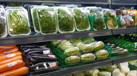 Image: A grocery store aisle of vegetables, all covered in plastic packaging.