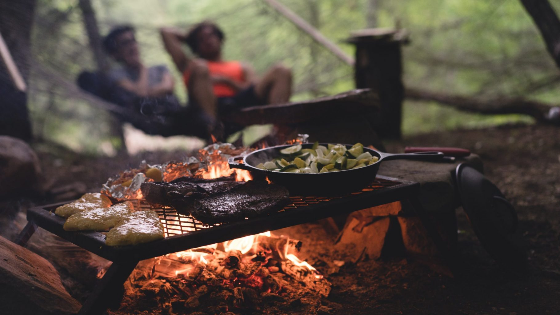 Image: Steak, potatoes, and vegetables cooking on a grate over a hot campfire.
