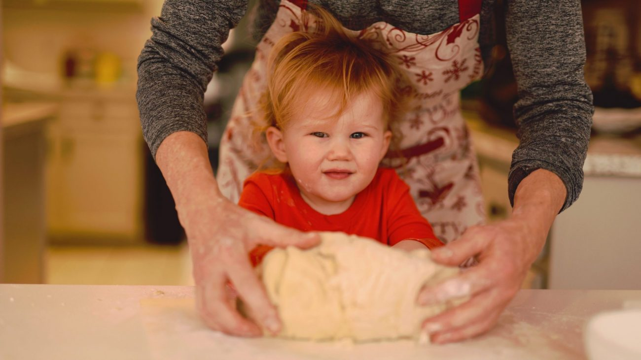 Image: A grandmother reaching over her grandson's shoulders to help him knead bread dough.