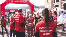 """Image: A woman standing among volunteers at a charity foot race, facing away from the camera wearing a red shirt that says """"volunteer team""""."""