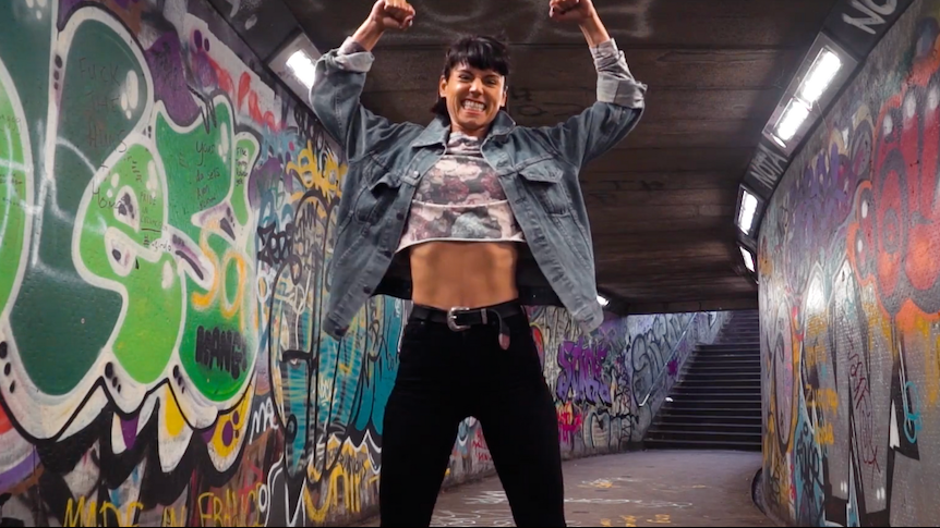 Image: Sorelle in a tunnel of graffiti, smiling and posing with her arms flexed above her head