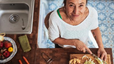 Image: A woman chopping vegetables and smiling at the camera