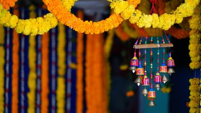 Image: Orange and yellow flower garlands hanging in the background and foreground, accompanied by a small wind chime. \