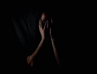Image: A person in the dark holding their head in their hands