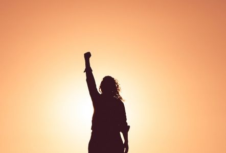 Image: The silhouette of a woman standing in front of a sunset orange background with her fist raised in the air.