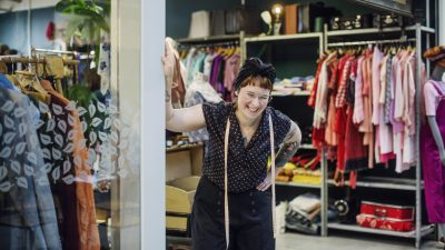 Image: A woman laughing, behind her are recycled clothes in a mall storefront.